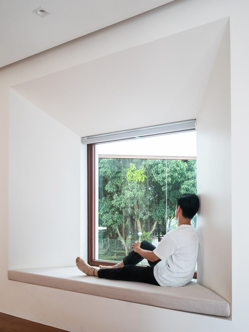The window near the family room has a built-in cushioned bench to serve as reading nook.