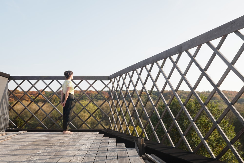 The balcony has a clear and sweeping view of the surrounding treetops and landscape.