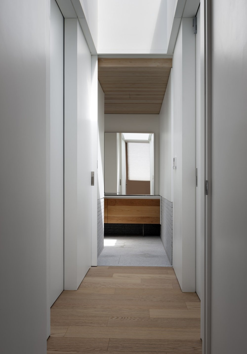 This is the hallway that leads to the bathroom with a view of the modern vanity on the far end topped with a large mirror.