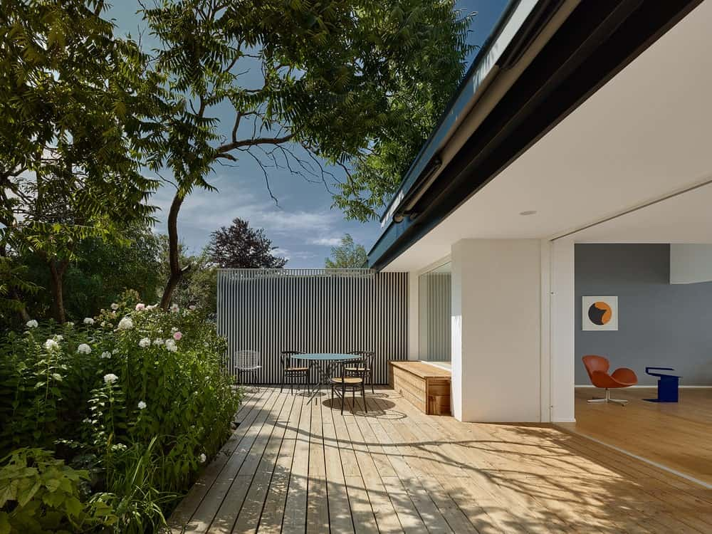 This is a look at the patio just outside the open walls of the house with a wooden shiplap walkway and an outdoor dining area on the far side.