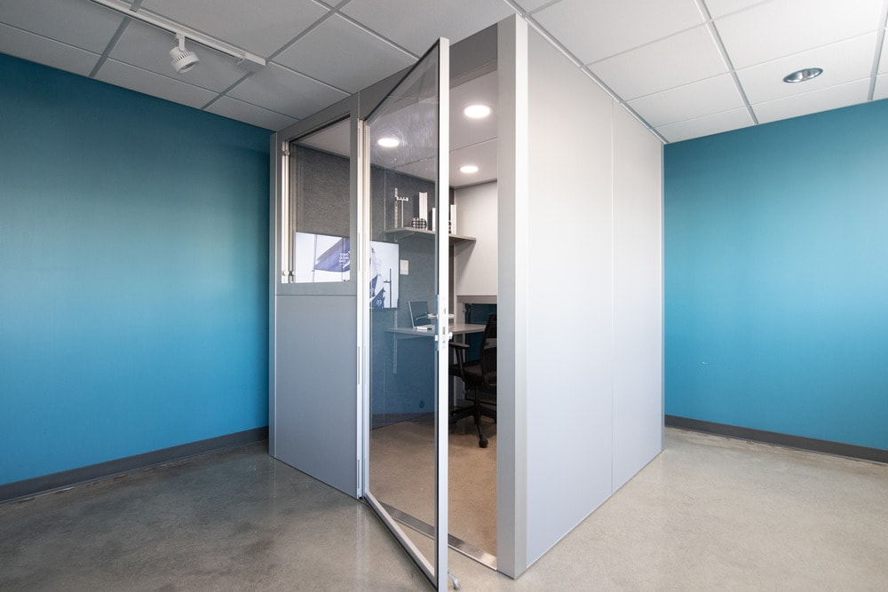 This is a fully-installed office pod located at the far corner of the room.