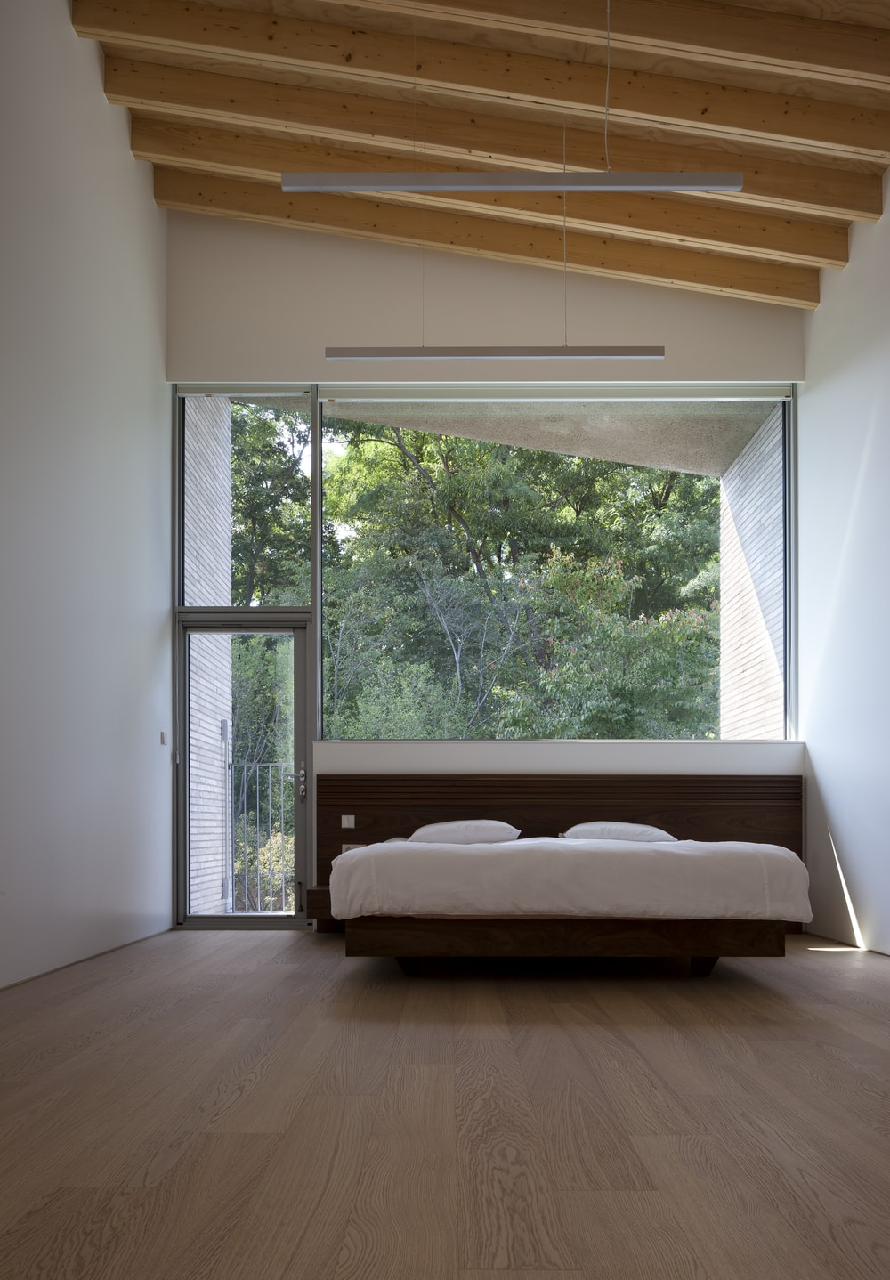 This simple and bright bed has a modern floating wooden platform bed that pairs well with the hardwood flooring. These are then complemented by the large glass wall and door that brings in natural lighting.