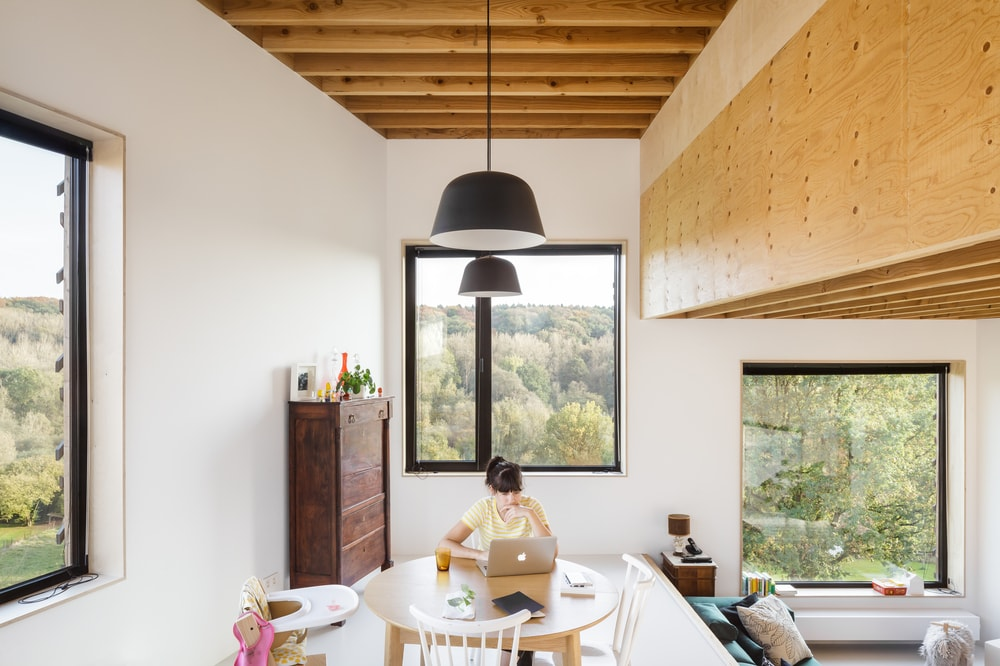 The dining area has a round wooden dining table topped with a black bowl pendant light that hangs from the wooden beamed ceiling above.