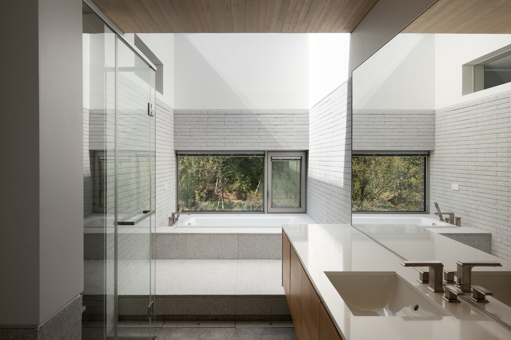 This is a closer look at the bathroom with a large modern vanity and a bathtub area on the far side bathed with sunlight from the skylight.