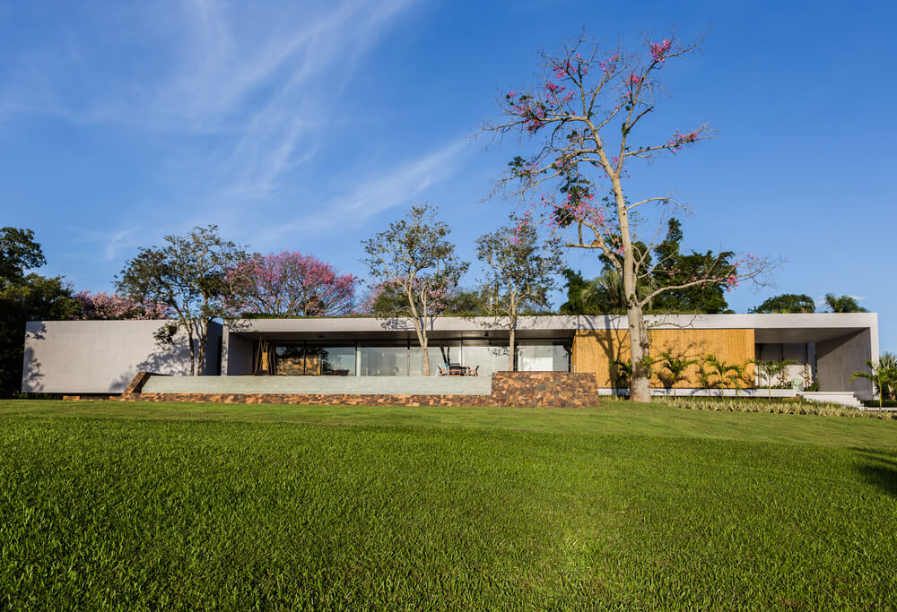 This is a look at the house that has wood and glass tones complemented by a lush landscaping of trees, shrubs and a large grass lawn.