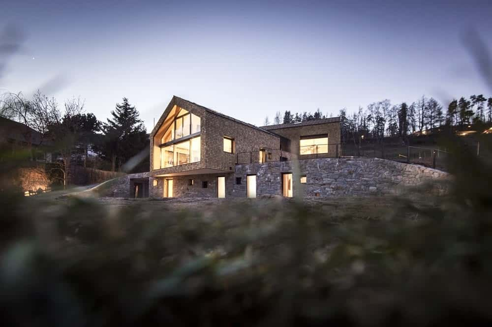 This is a nighttime view of the house with textured stone exteriors complemented by the multiple windows and the large glass wall that all glow warmly coming from the interior lights.