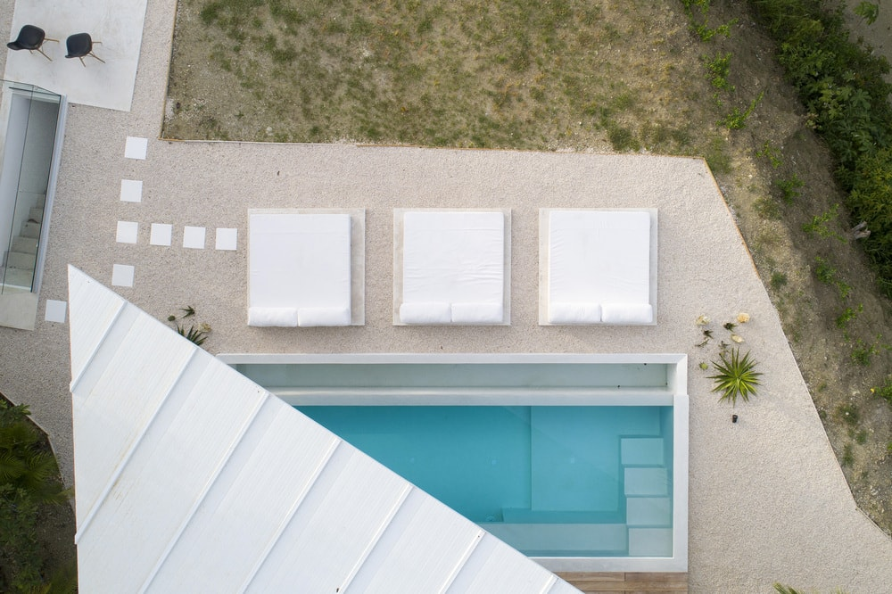 This is an aerial view of the back of the house with a pool. You can also see here the unique design of the roof.