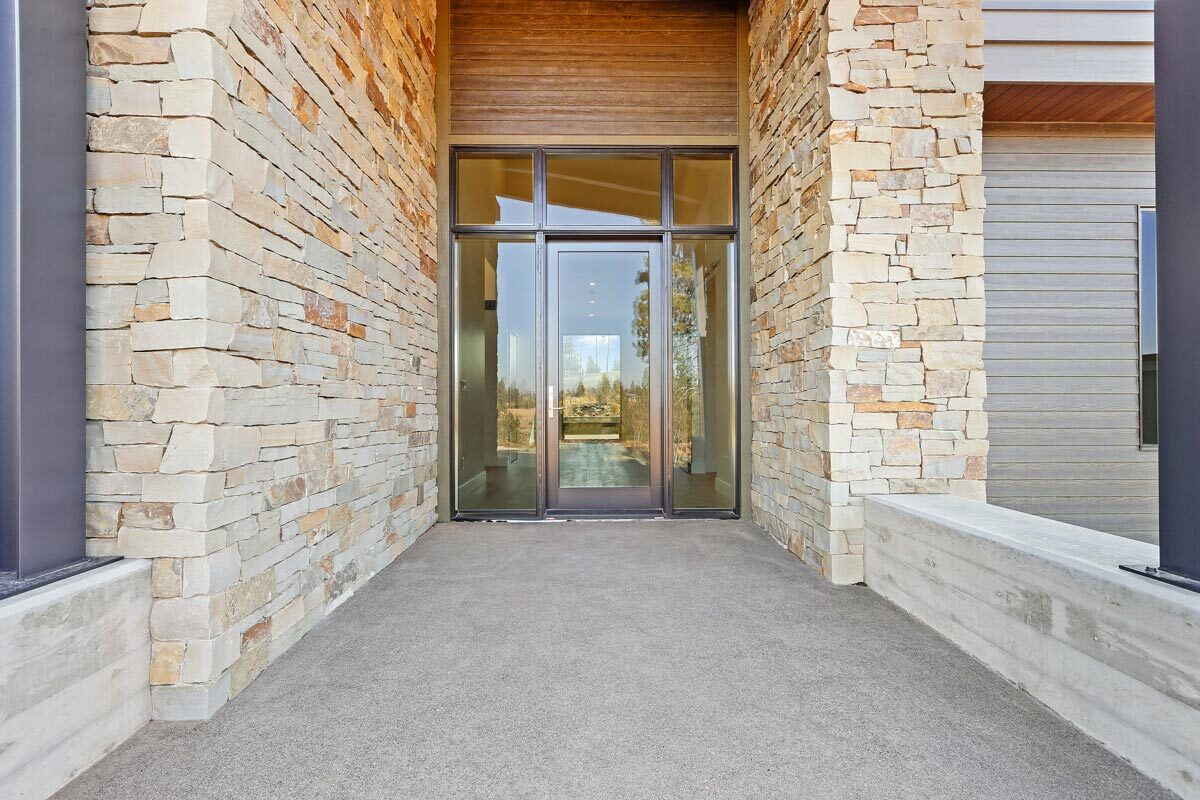 A closer look at the home entry with a glass front door flanked by brick walls.A closer look at the home entry with a glass front door flanked by brick walls.