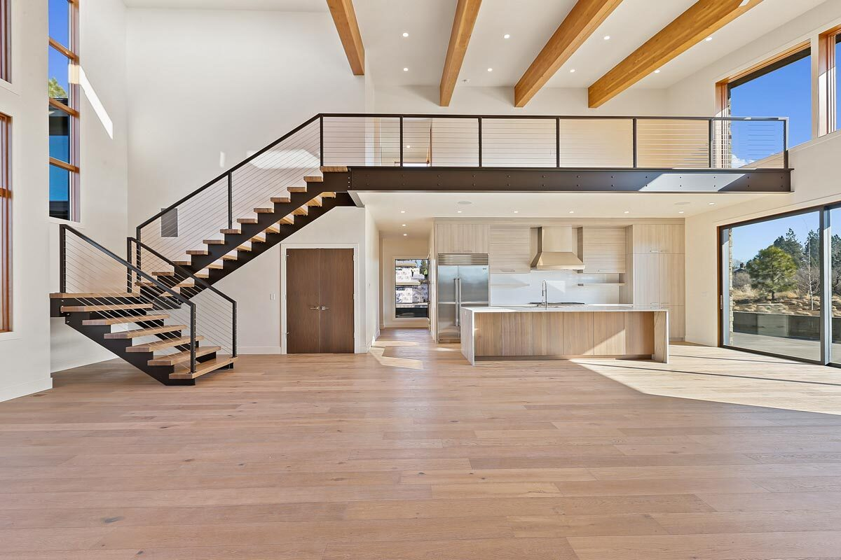 The modern staircase leads to an open loft situated above the kitchen area.