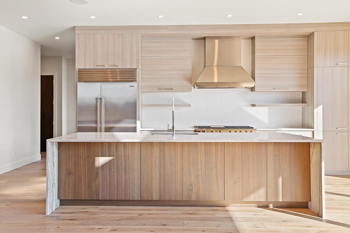 Kitchen with light wood cabinetry, stainless steel appliances, and a marble top island.