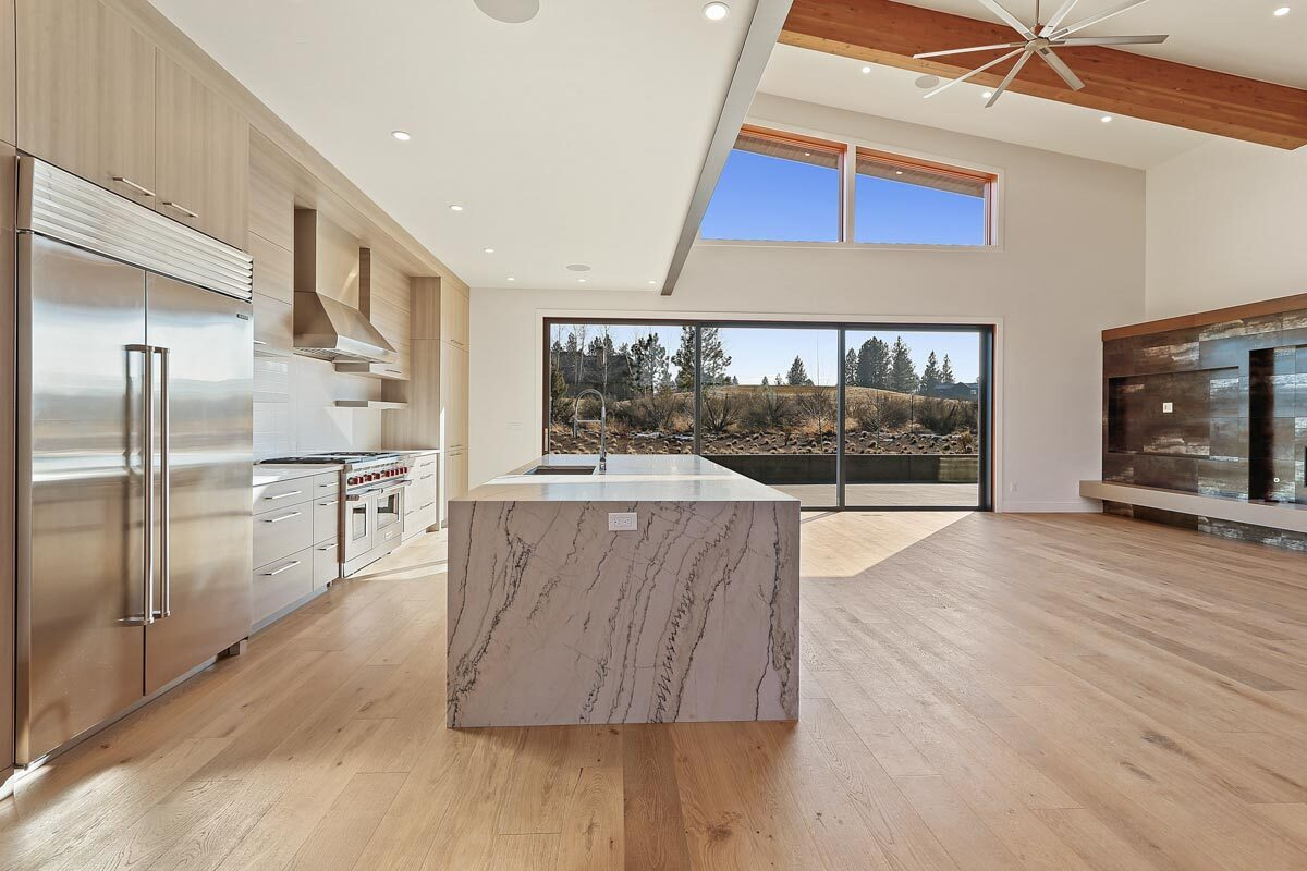 An open layout view of the kitchen and living room topped by a beamed ceiling.