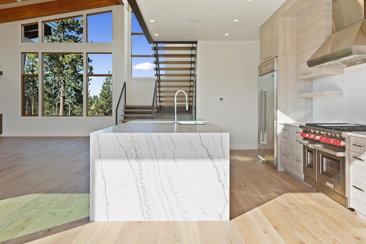 Opposite view of the kitchen showing the modern staircase and clerestory windows in the dining area.
