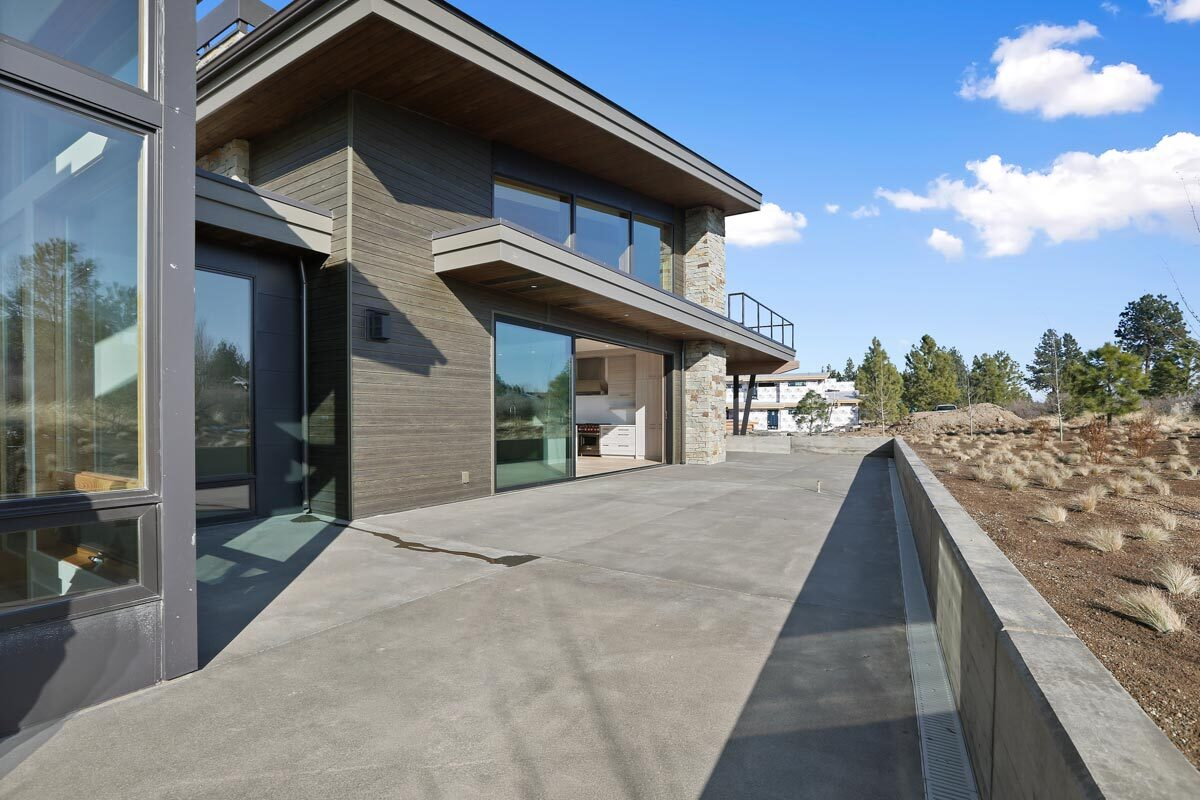 The rear patio with concrete flooring runs the width of the house.