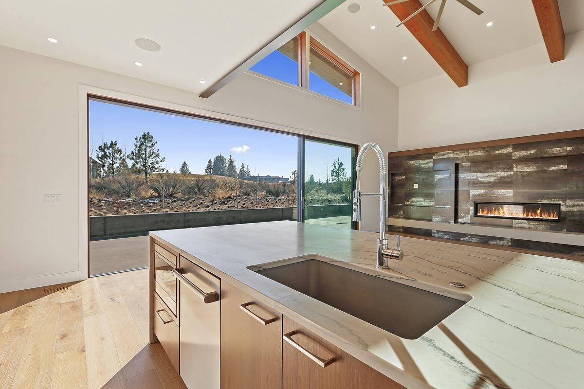 The kitchen island is fitted with, a dishwasher, an oven, and an undermount sink paired with a gooseneck faucet.