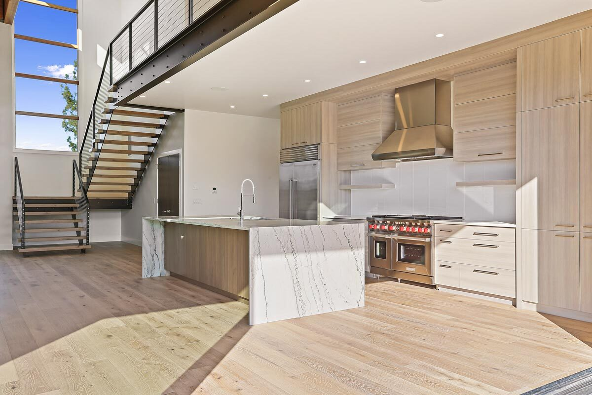 Recessed ceiling lights along with a sliding glass door and tall window above the staircase brighten the kitchen.