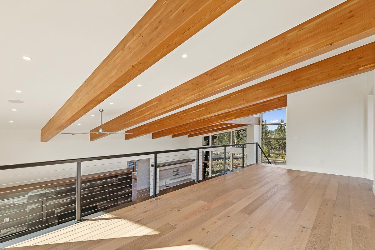 The open loft has wide plank flooring, a beamed ceiling, and metal railings.