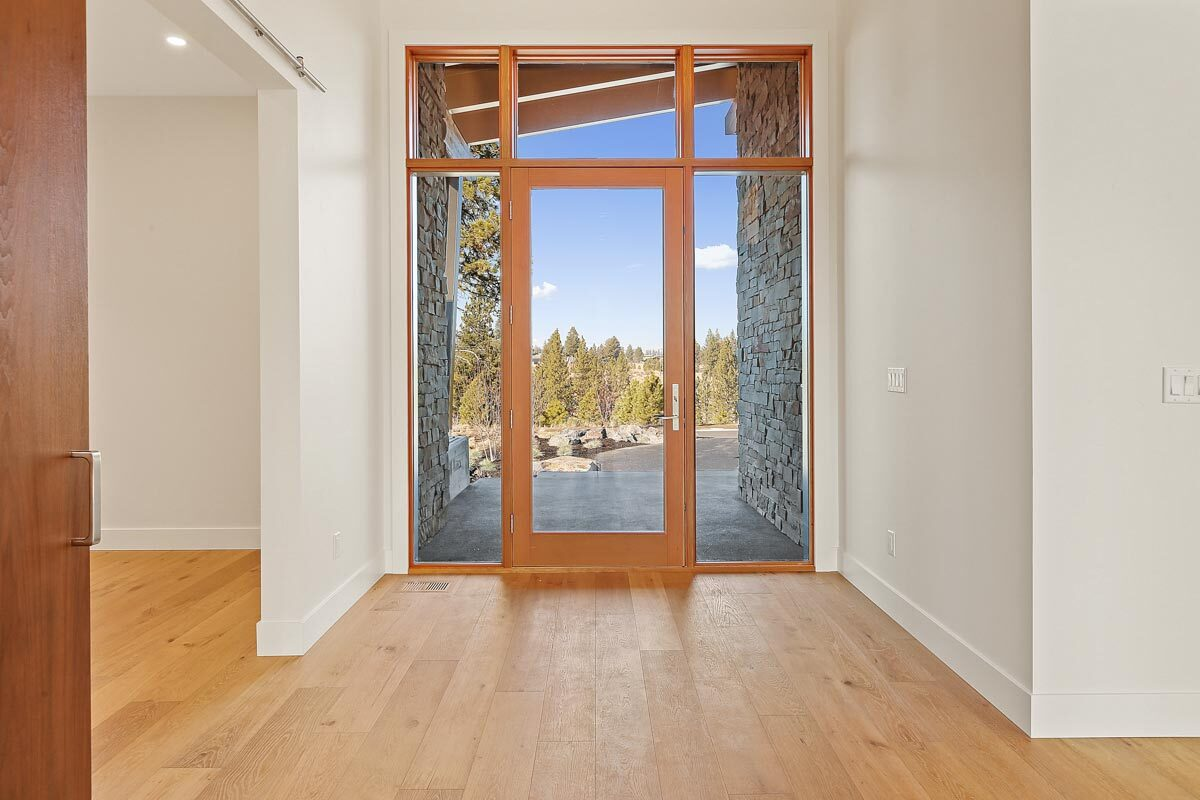 Wood trims accentuate the main glass door surrounded by sidelights and a transom window.