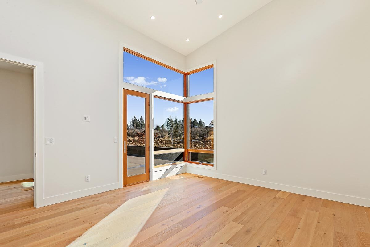 Primary bedroom with vaulted ceiling, hardwood flooring, corner glass windows, and rear patio access.