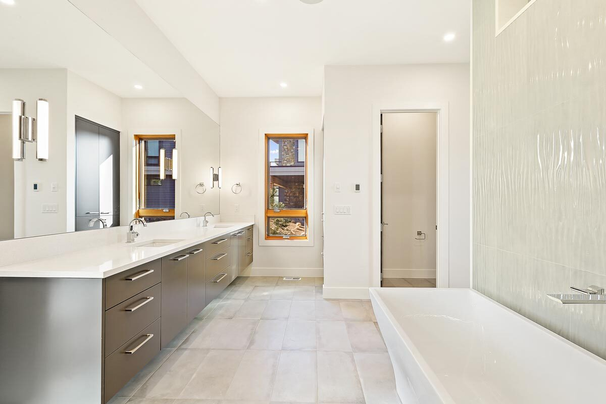 The primary bathroom is equipped with a dual sink vanity, a freestanding tub, a walk-in shower, and a toilet room.
