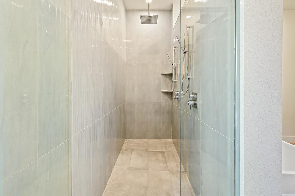 The walk-in shower has tiled walls, chrome fixtures, and corner shelves.