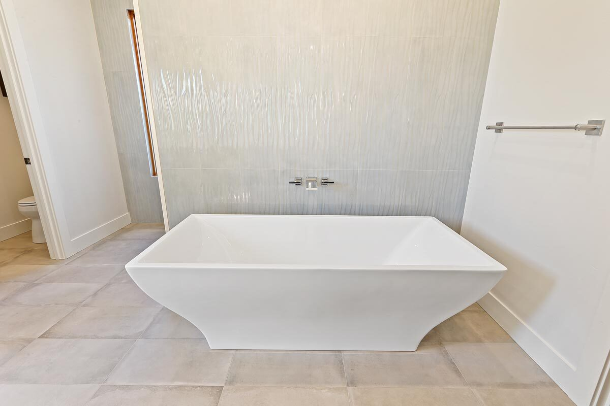 A close-up look at the freestanding tub over tiled flooring.