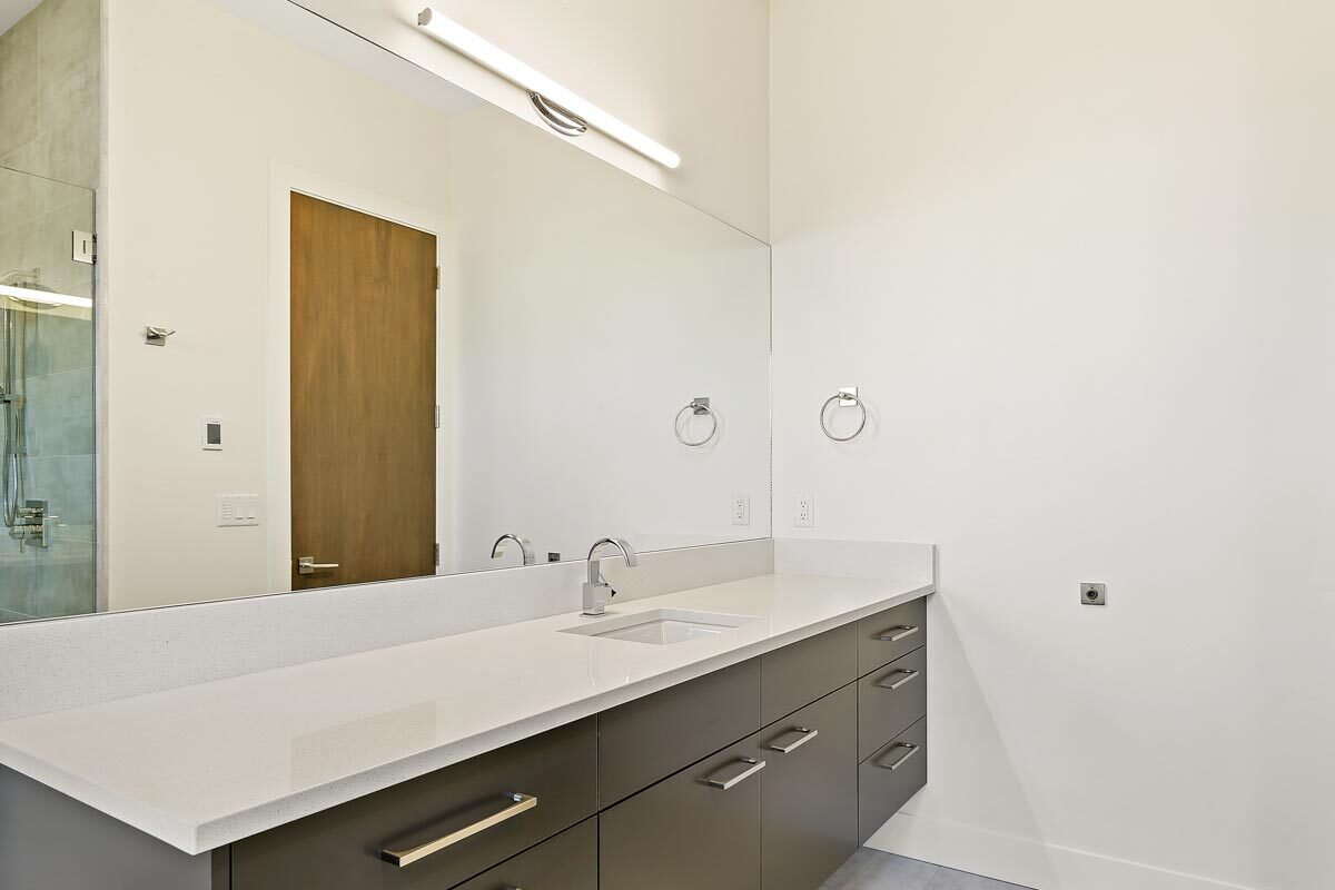 Dark wood vanity with quartz countertop, an undermount sink, and a large frameless mirror.