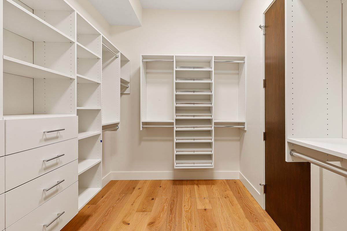Primary walk-in closet with built-in shelves and drawers that blend in with the white walls.