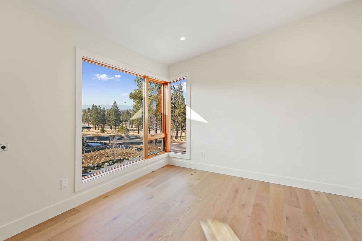 This bedroom has wide plank flooring and white walls fitted with corner windows.