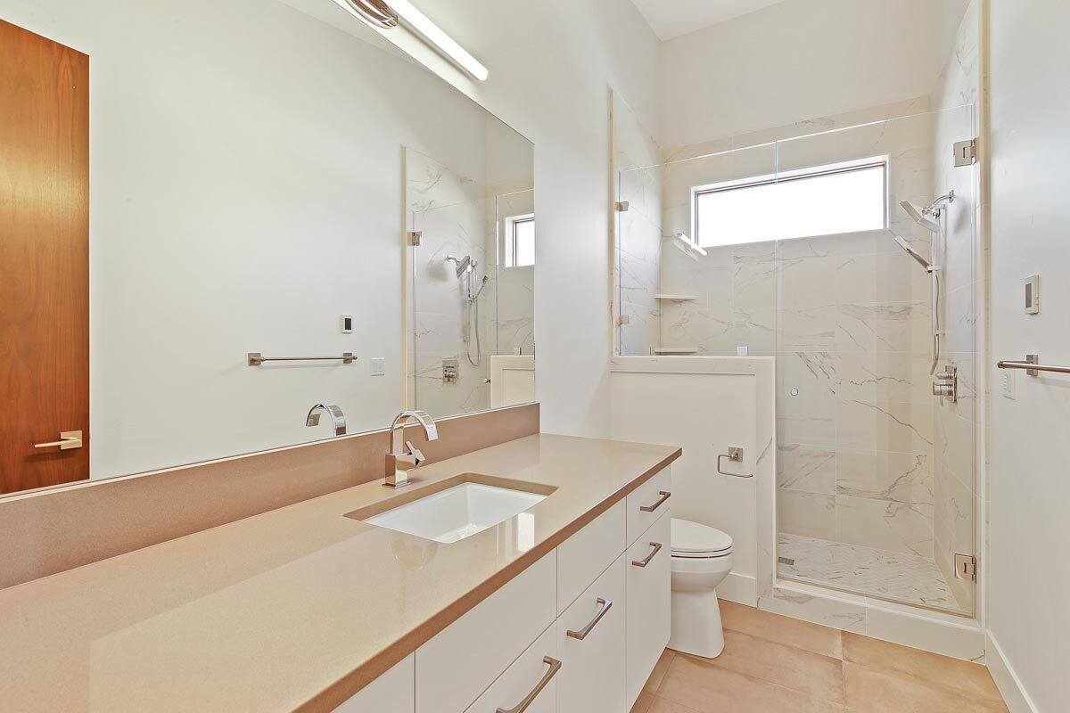 Bathroom with a sink vanity, a toilet, and a walk-in shower.