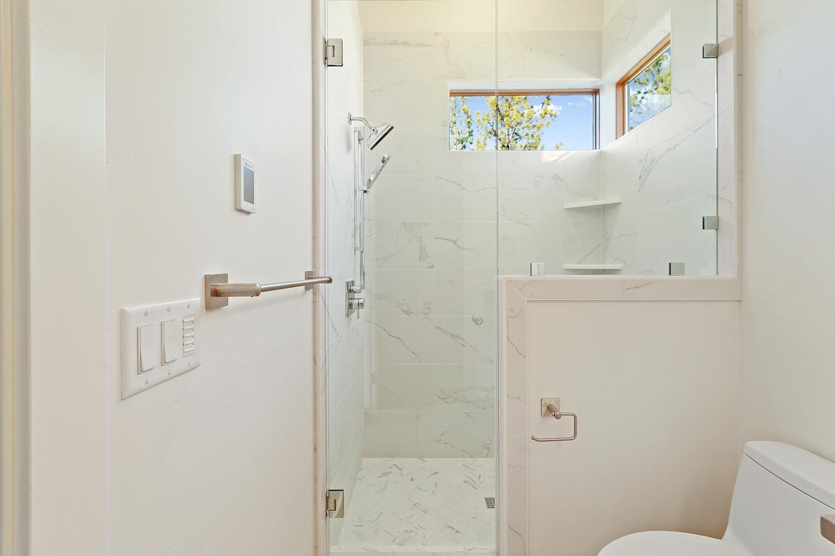The walk-in shower has chrome fixtures, corner shelves, and marble walls that extend to the tiled flooring.