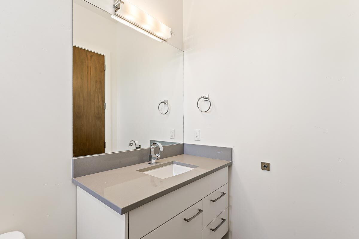 Powder room with a white vanity showcasing a quartz countertop and a frameless mirror well-lit by a linear sconce.