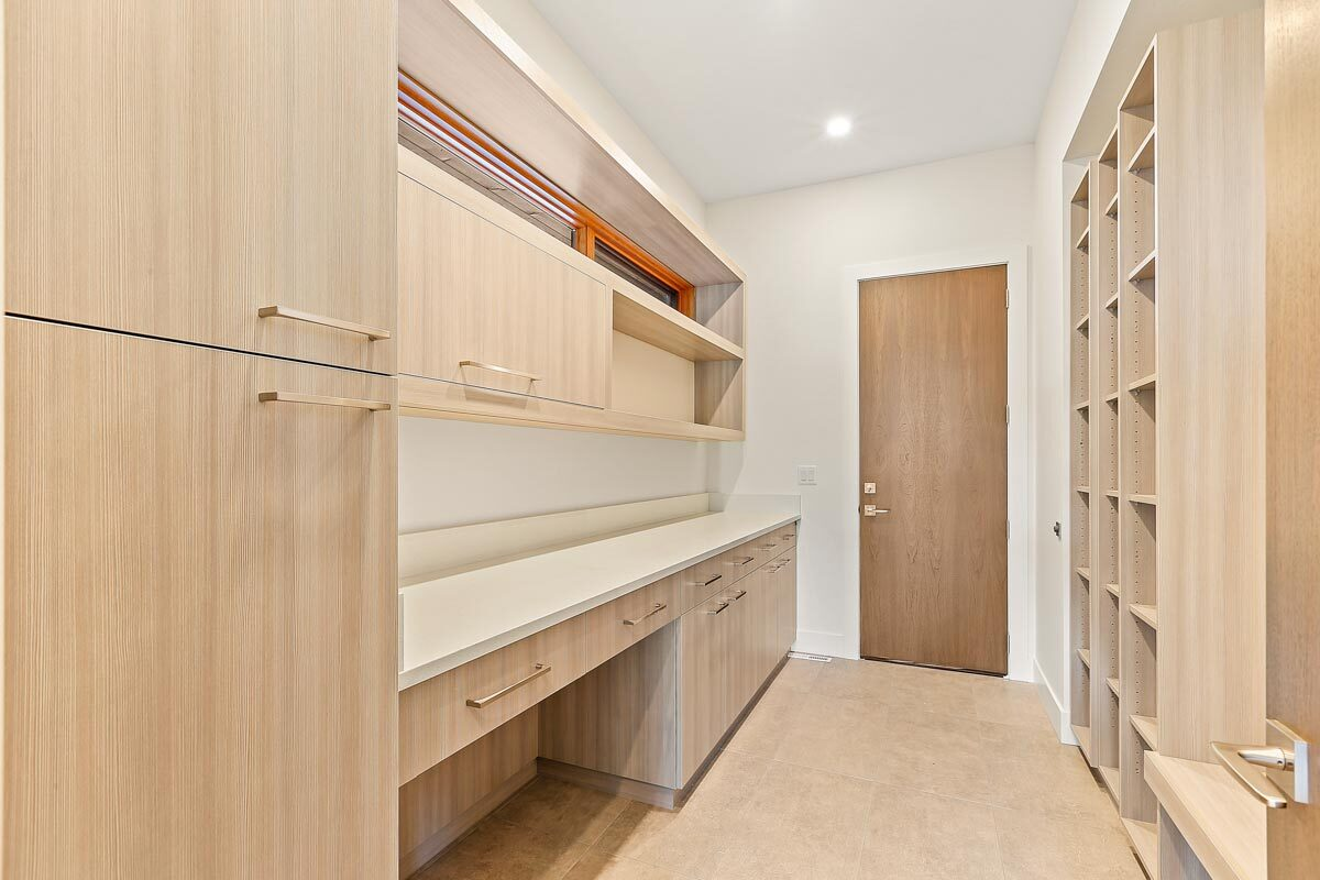 Mudroom with natural wood cabinets, a counter, and floating shelves.