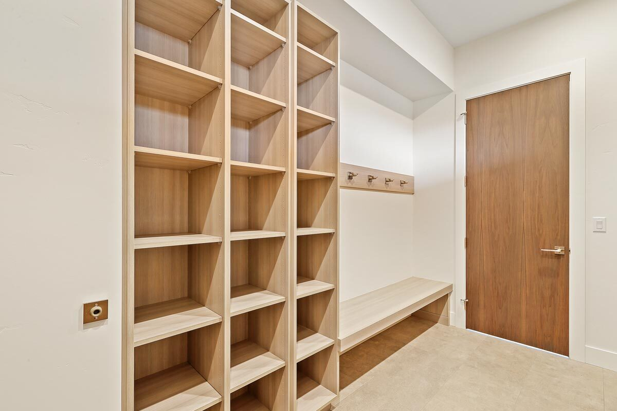Wooden shelves, a built-in bench, and a hook rack complete the mudroom.