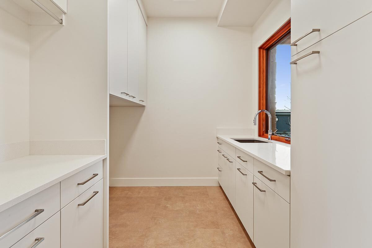 Utility room with white cabinets and a sink placed under the picture window.