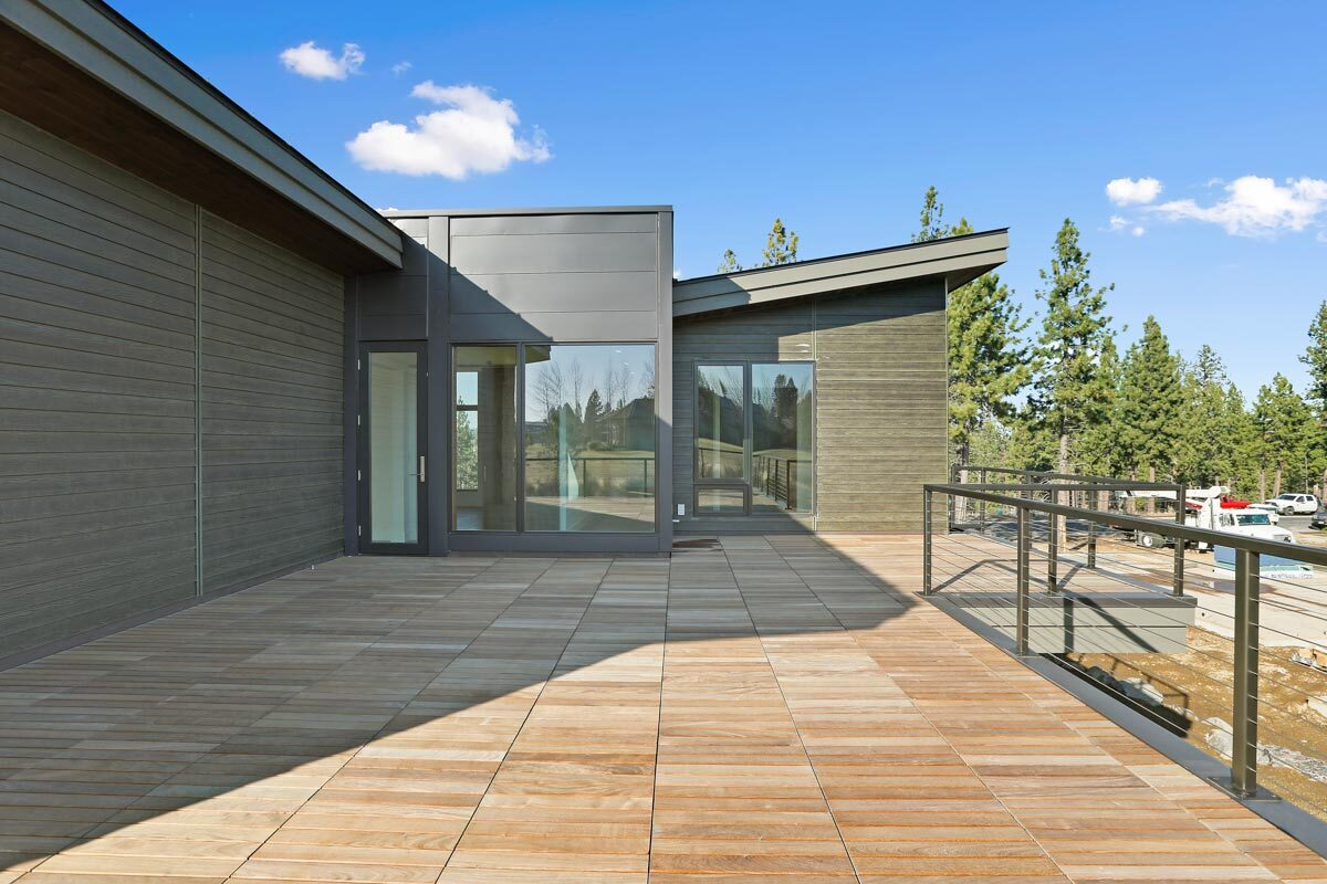 An open deck with wood tile flooring and metal railings.
