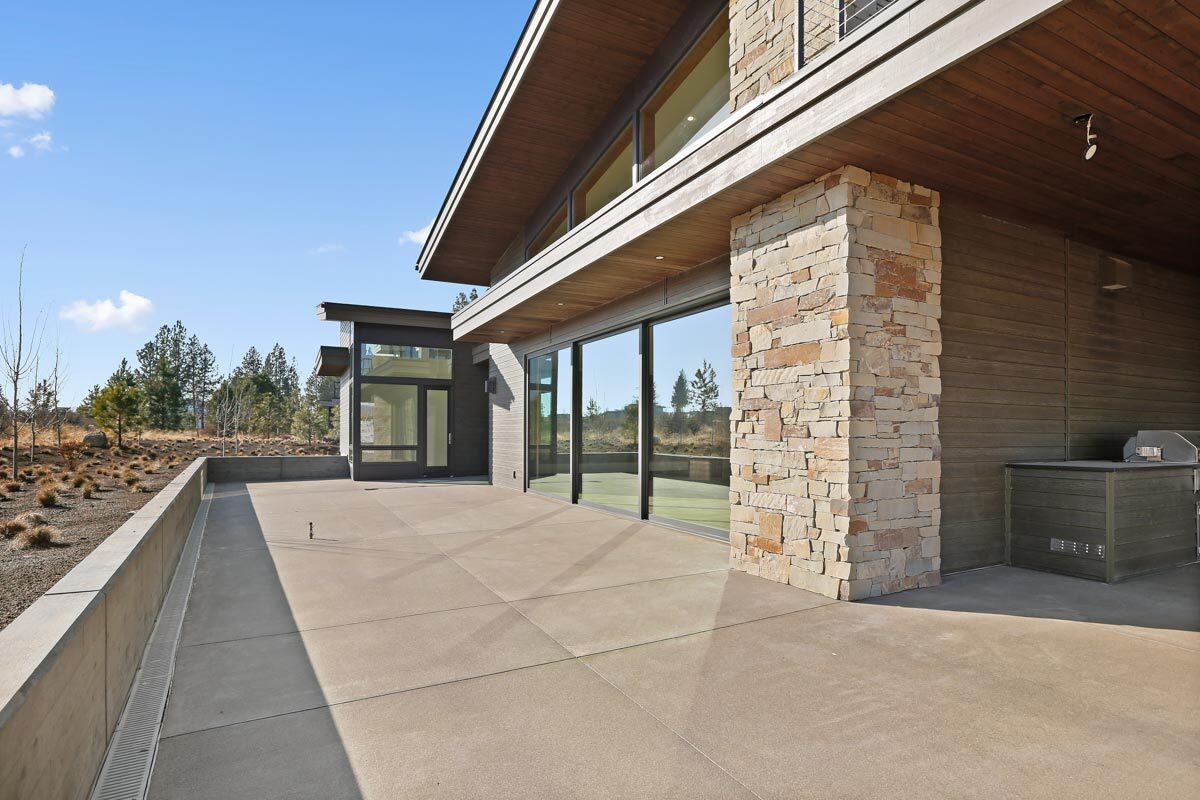 The open patio has concrete tile flooring framed with retaining walls.