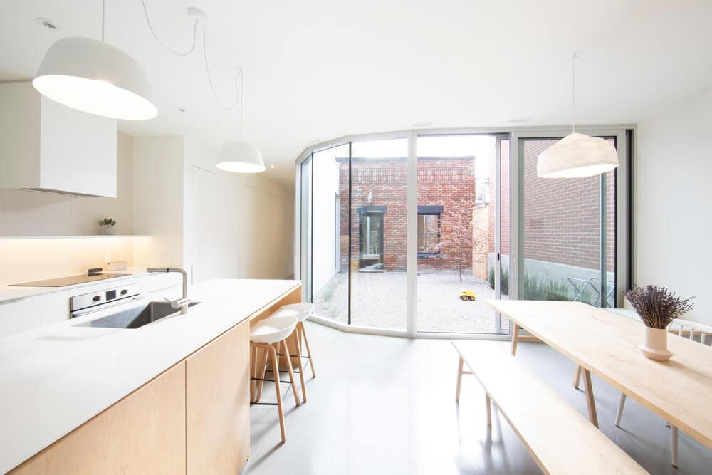 This is a close look at the interior of this minimalist home that has wooden elements that complement the pure white walls, ceiling and countertops brightened by the natural lights coming in from the glass wall on the far side.