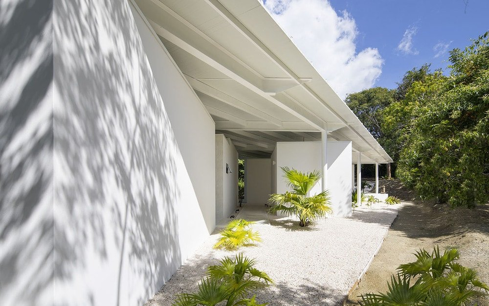 This is a side of the house with white pebbles on the ground that surround the tropical plants that give a dash of color to the bright exterior walls.