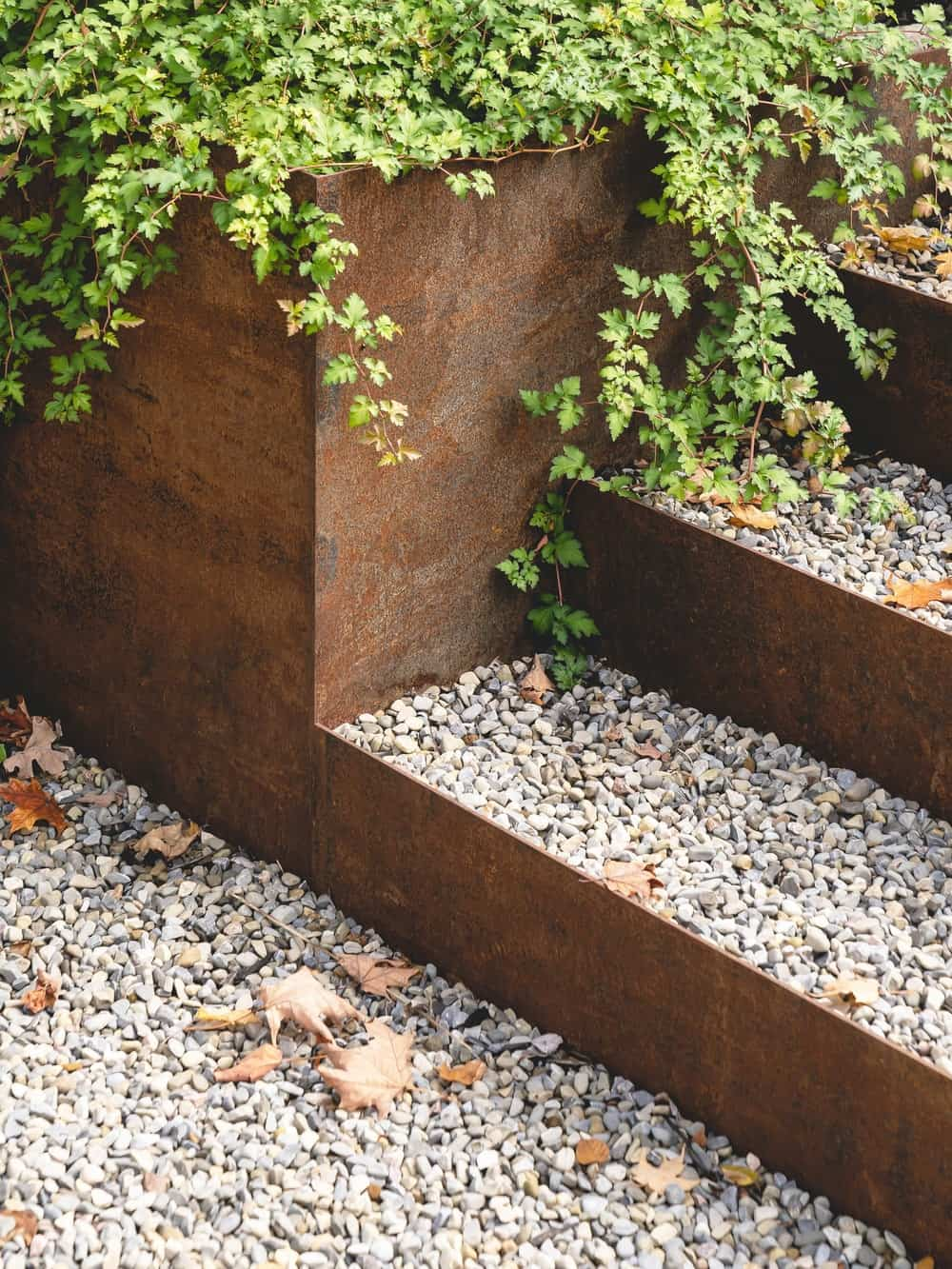 This close look at the steps outside the house with gravel and plants on the planters.