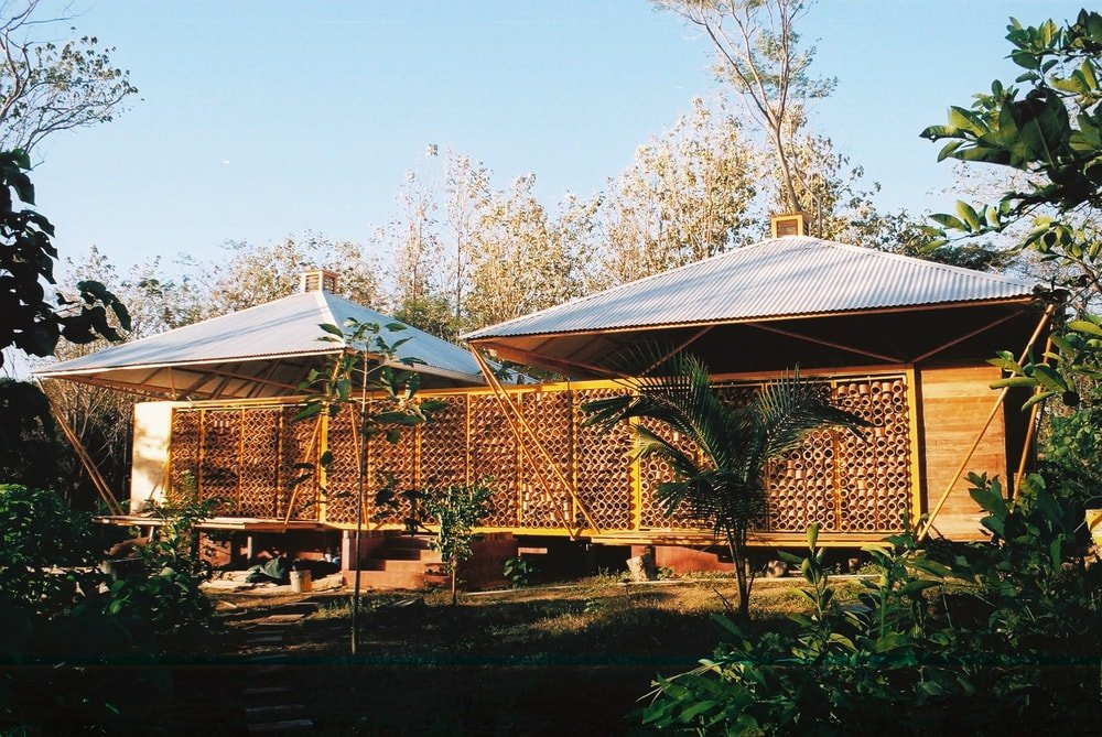 This is a look at the exterior of the house with two roof structures above and patterned panels on its exterior walls that let in natural lighting.