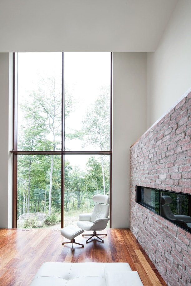 This is a close look at the interior of the house that has a modern fireplace by the large glass wall.