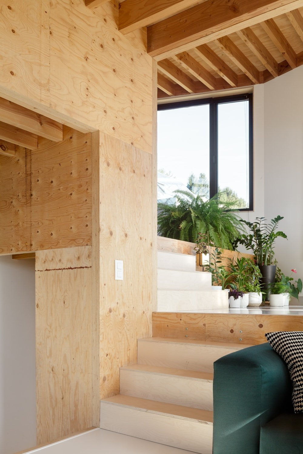 The wooden steps on the side of the sofa matches well with the wooden pillars, walls and beamed ceiling.