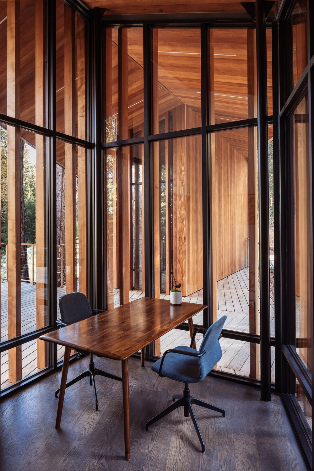 This is an interior view of the glass wall fitted with a simple home office by the corner.