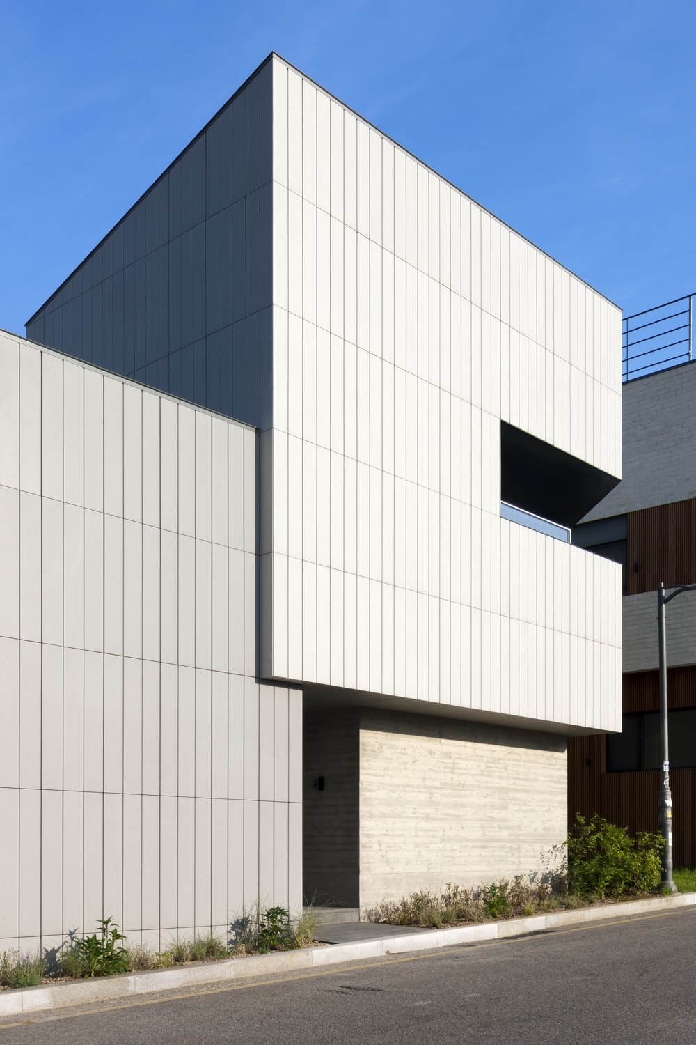 This view of the front of the house shows the shrubs that line the walls to complement the light gray modern panels.