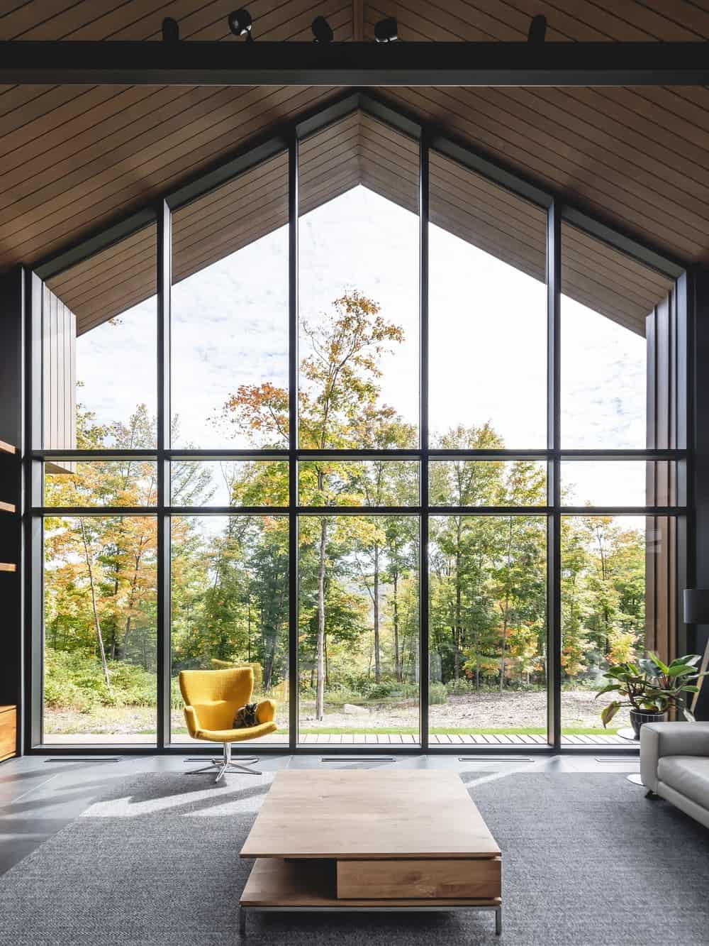This is an interior look at the living room with a tall ceiling and a large glass wall that showcases the tall trees outside.