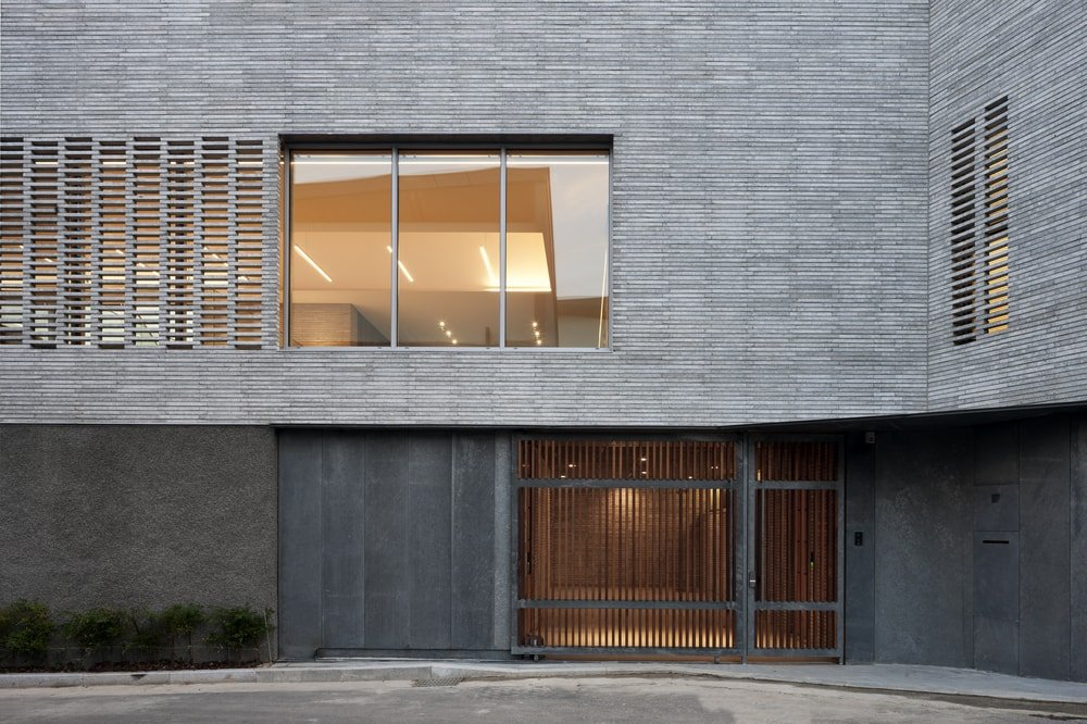 The warm lighting of the windows and doors from the interiors match well with the gray tone of the exterior walls.