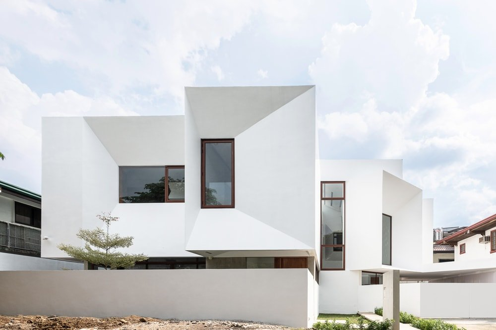 This is a view of the front of the house with large glass windows that stand out against the bright white exterior walls.