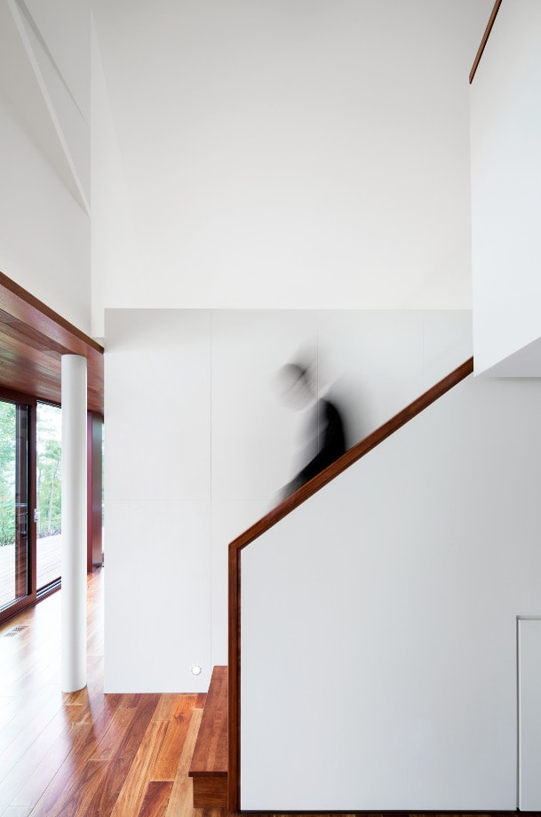 This is a side view of the staircase that has wooden banisters that match the hardwood flooring contrasted by the white walls.