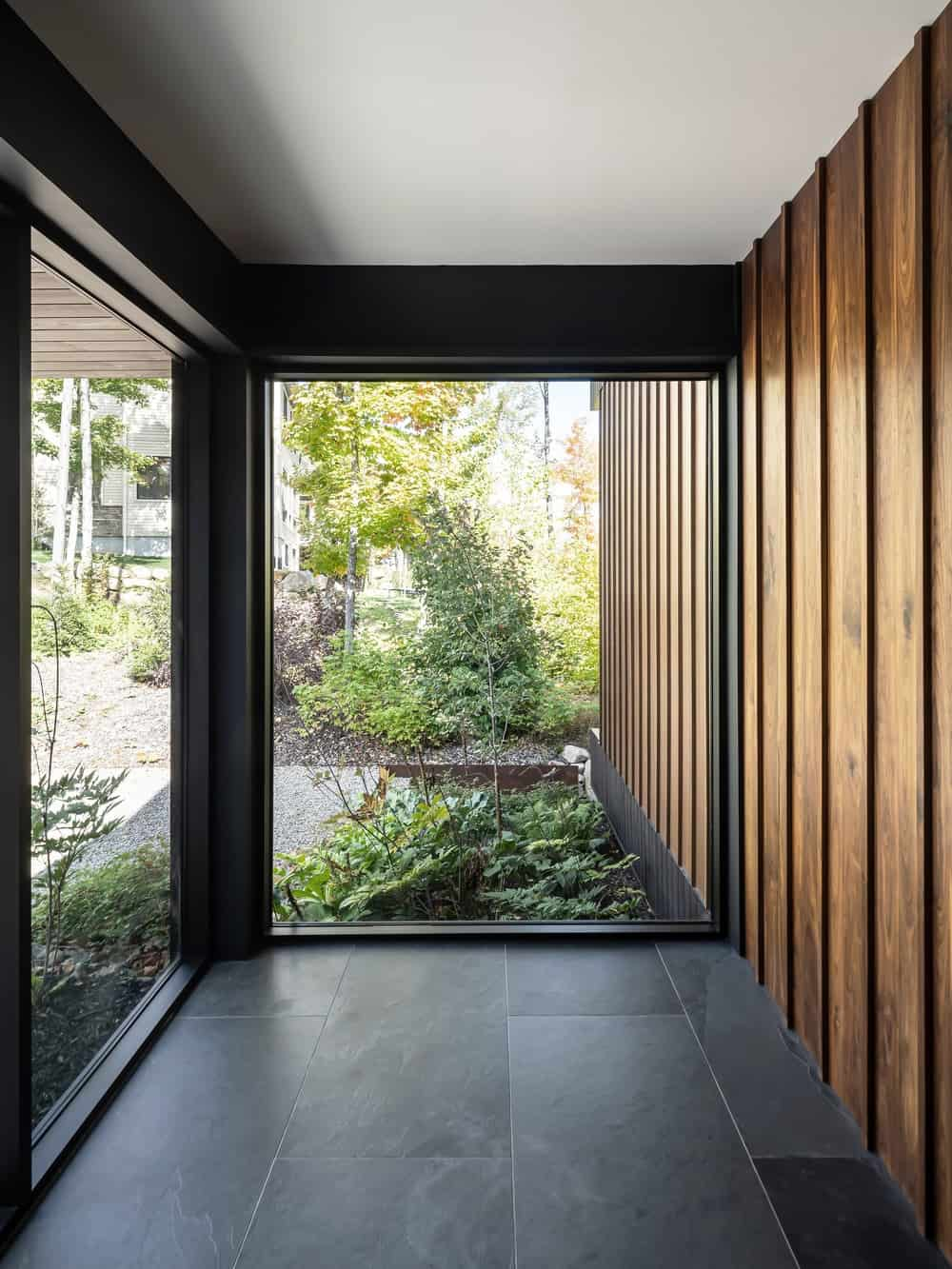 This is a close look at the glass walls of the side of the house that has a clear view of the plants outside in the landscape.