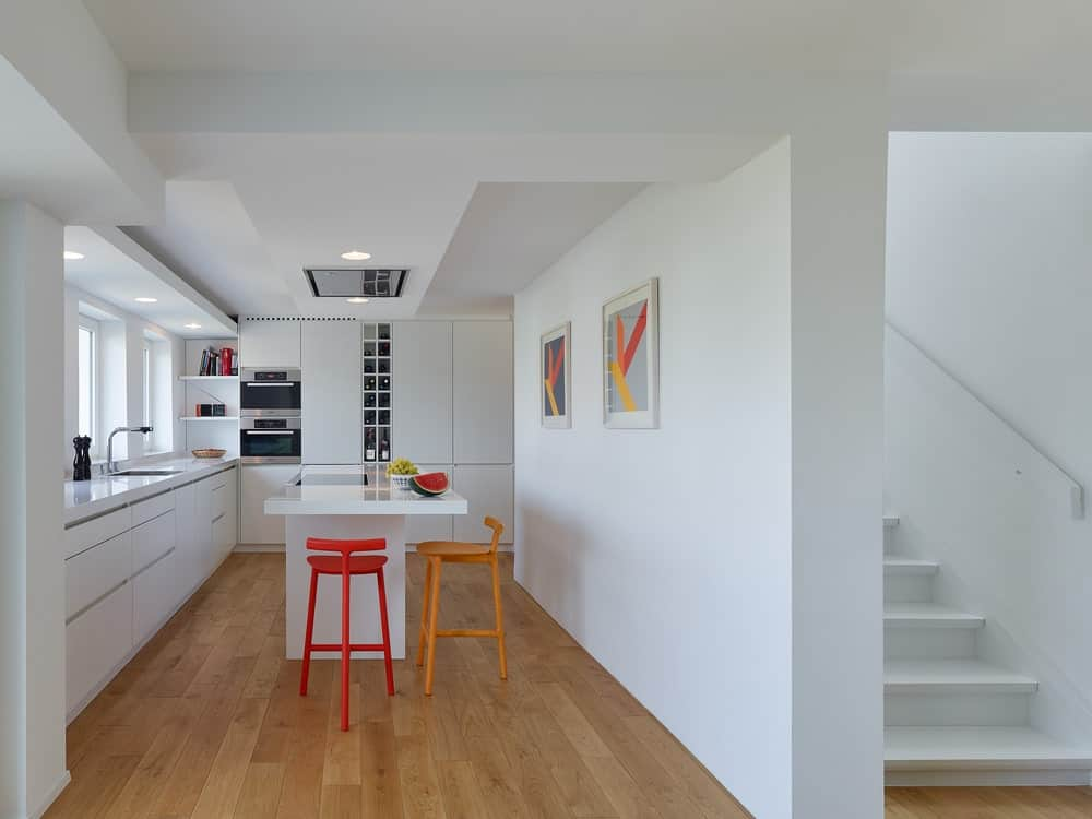 This is the kitchen with a white kitchen island that makes the orange stools stand out. This also gives a modern and clean vibe that matches the wall-mounted art works.
